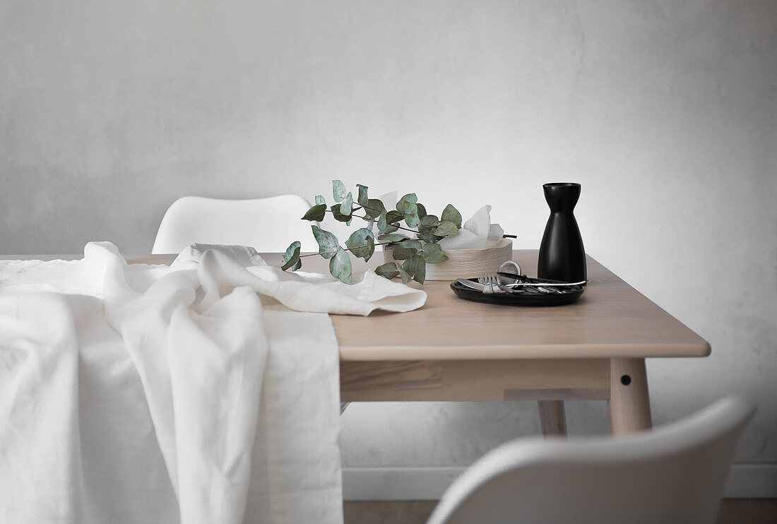 White tablecloth, cutlery, carafe and eucalyptus branch on table