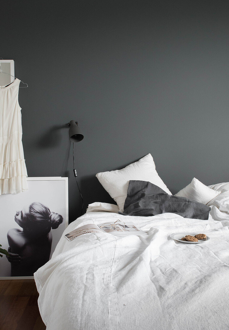 Plate of biscuits on bed with white bed linen, reading lamp on grey wall and black-and-white photograph