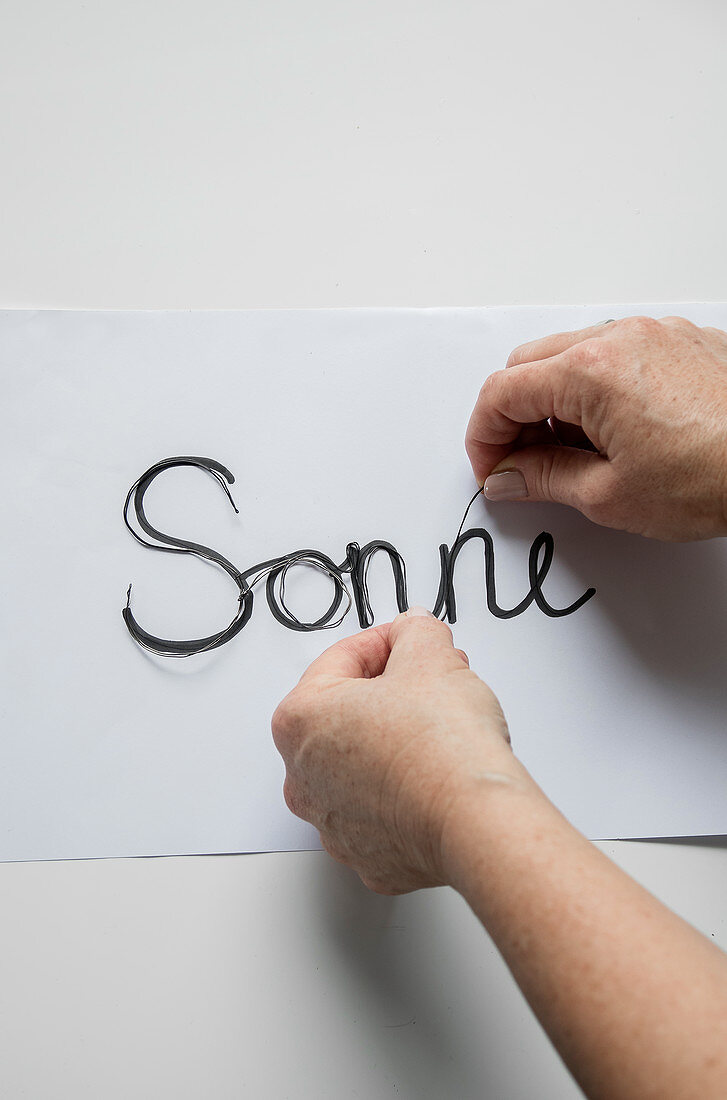 Hands bending wire to make the word 'Sonne' (sun)