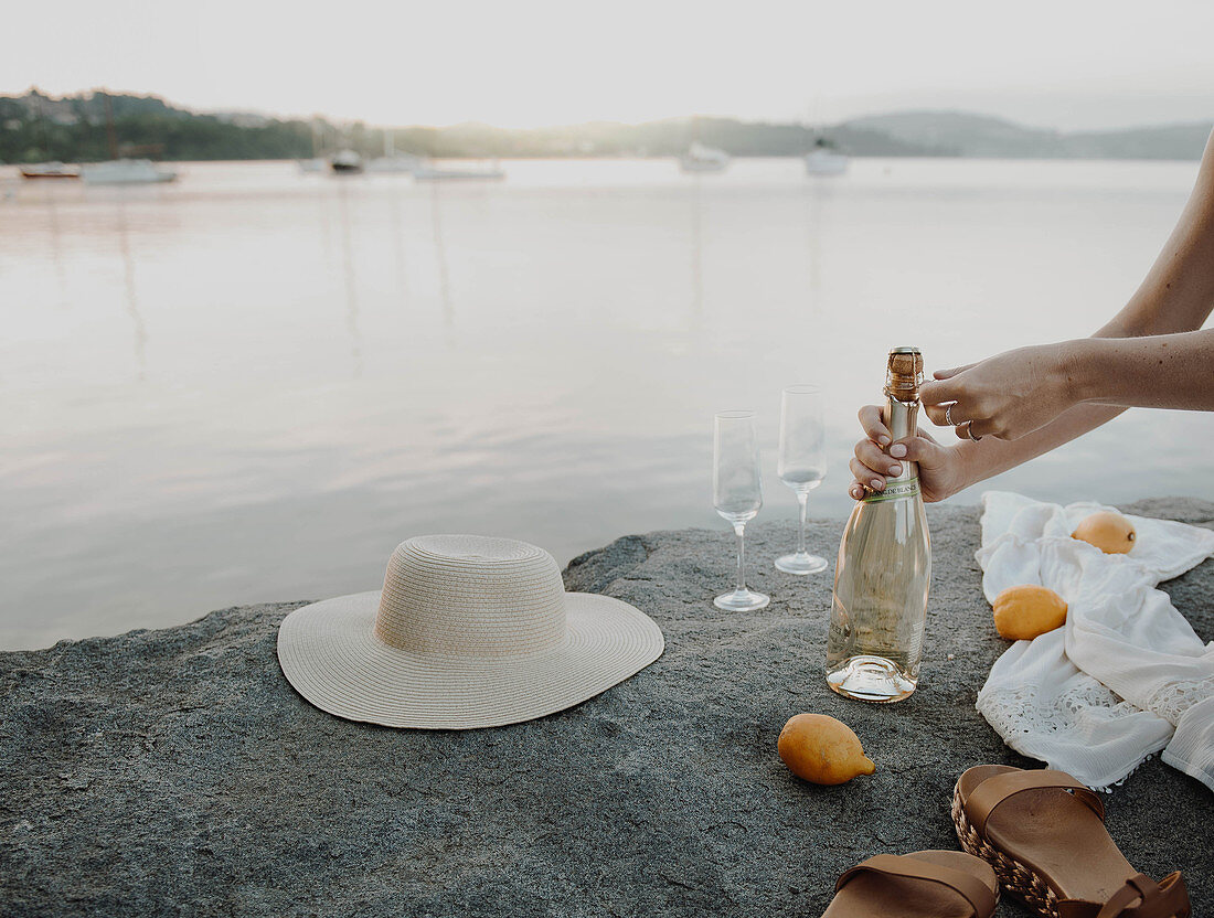 Woman opening glass of sparkling wine for picnic on shores of lake