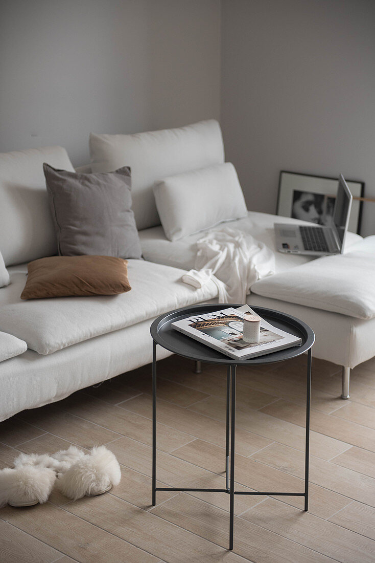 Fluffy slippers next to white chaise sofa