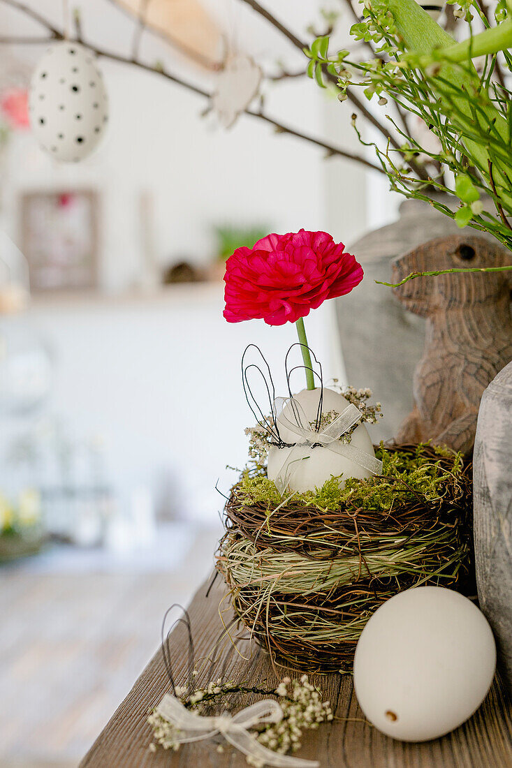 Blown egg and ranunculus in Easter nest