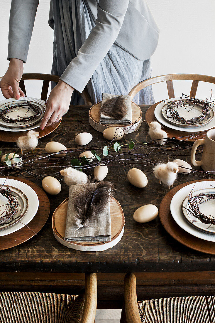 Woman setting old wooden table with rustic natural decorations