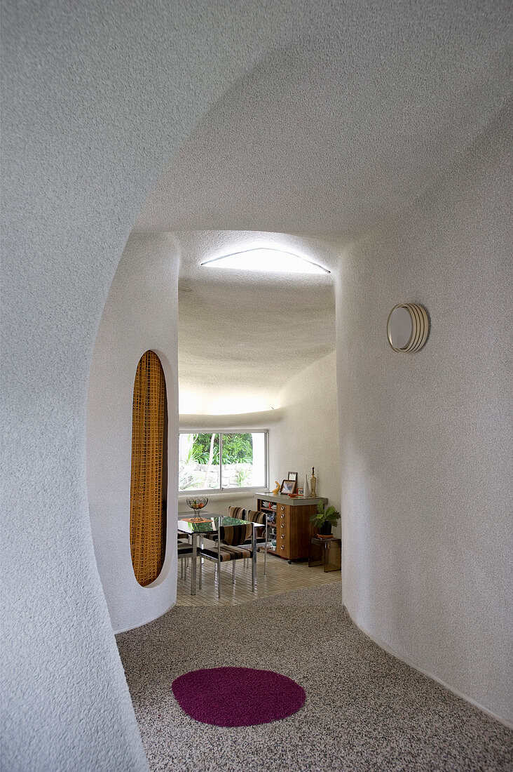 Hallway with organically formed walls and retro dining room