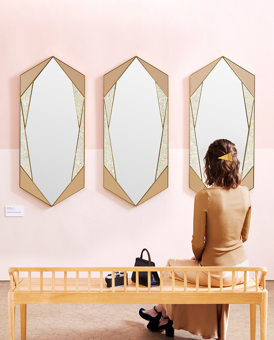 Woman sitting on bench in front of three mirrors on pink wall