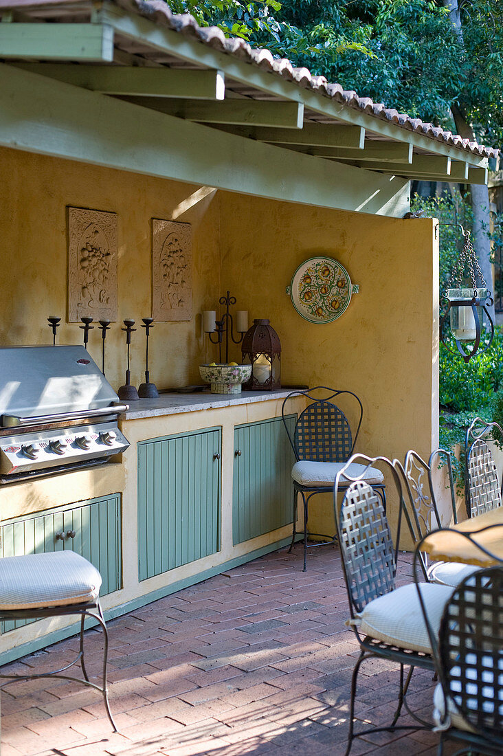 Roofed outdoor kitchen with barbecue on terrace in vintage country-house style