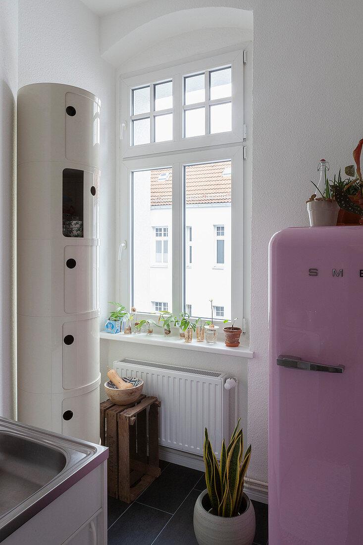 Pink fridge next to window and round cabinet in kitchen