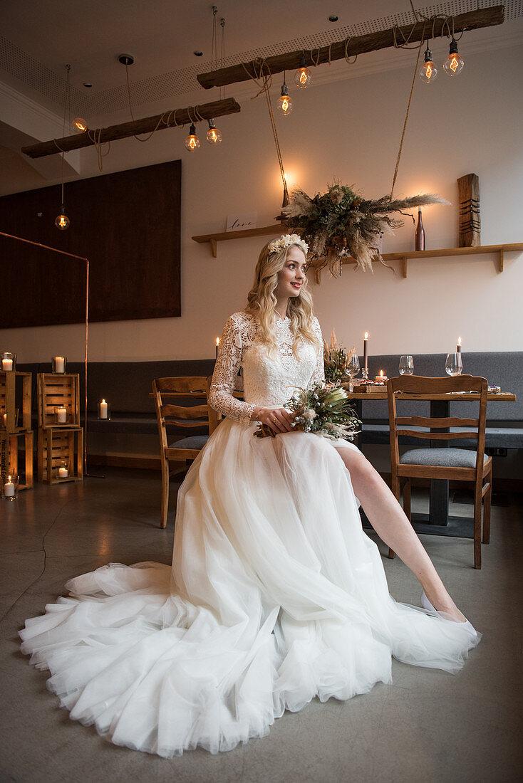 Bride wearing white wedding dress with train in vintage-style restaurant
