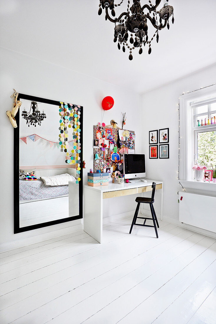 Desk and large black-framed mirror in teenager's bedroom decorated in white