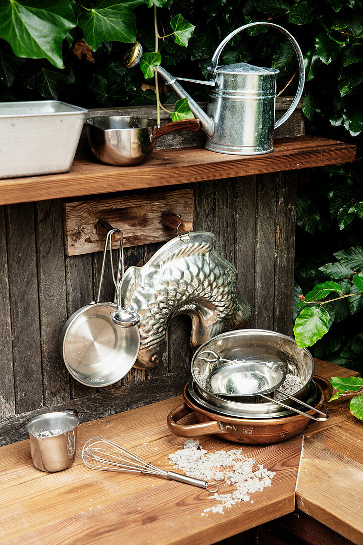 Pans, cake tins and kitchen utensils in outdoor play kitchen