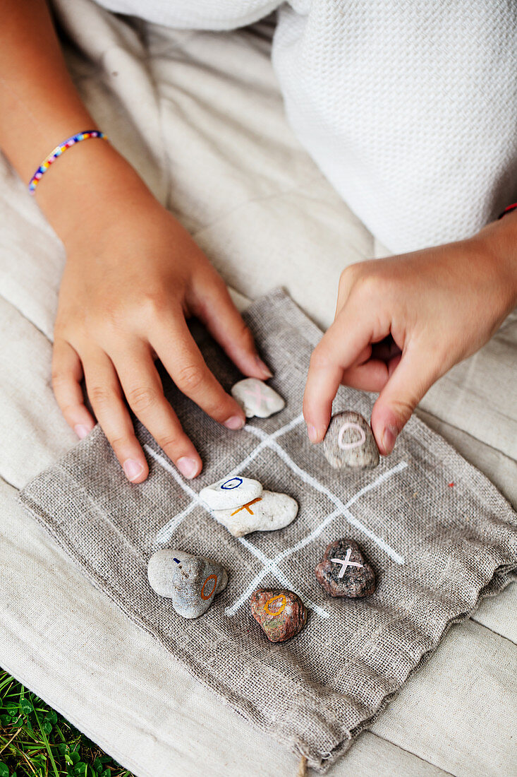 Hands of children playing noughts and crosses using painted pebbled
