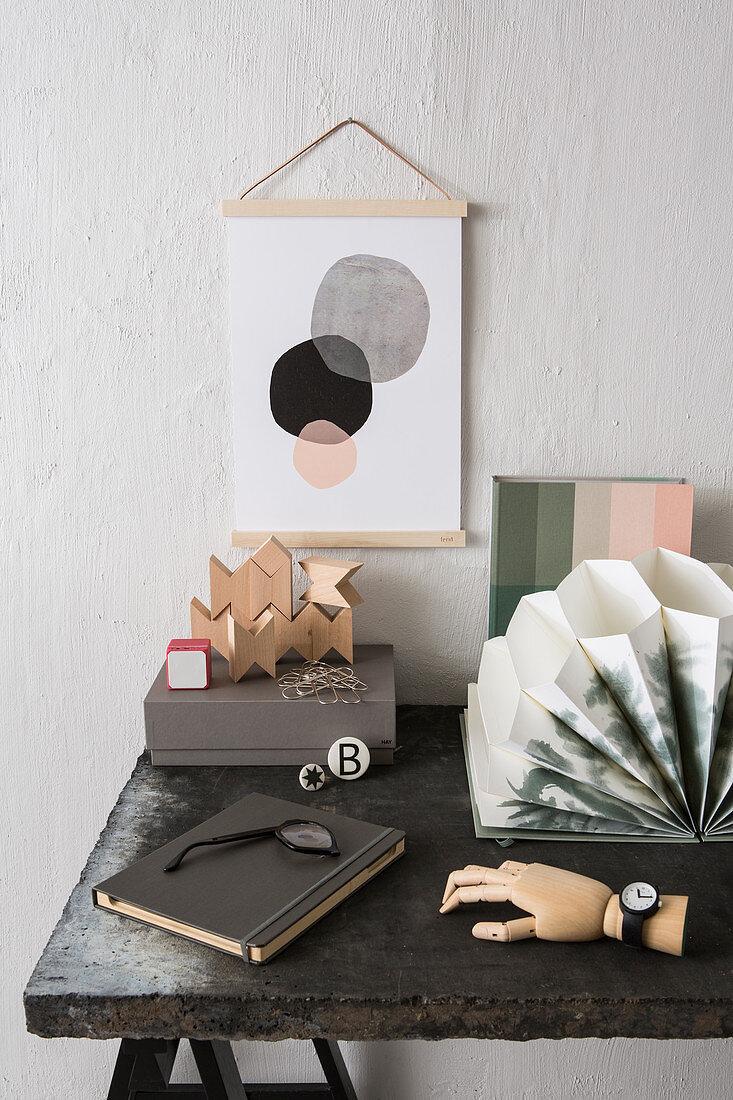 Still-life arrangement on desk: wooden blocks, accordion folder, note book and wooden hand wearing watch