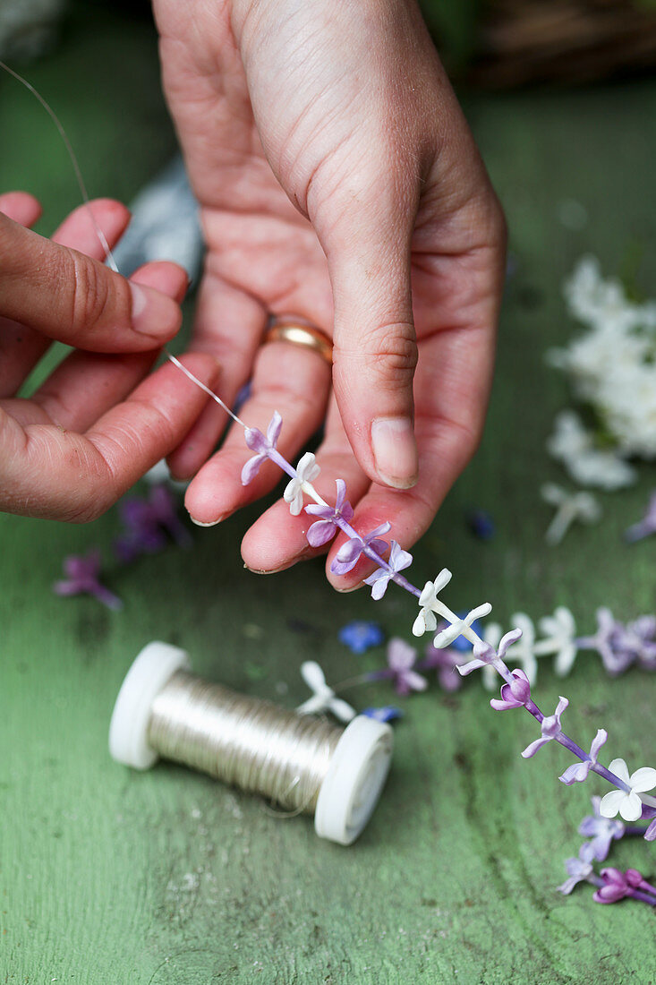 Woman threading lilac florets onto fine silver wire