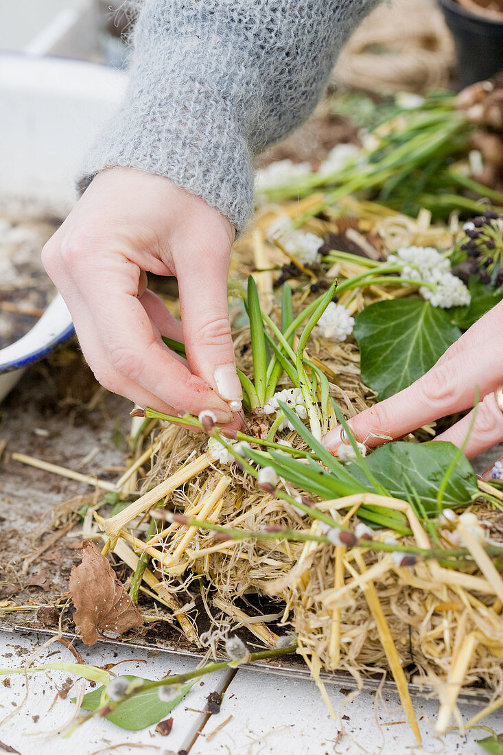 Attaching grape hyacinths to a straw Easter wreath