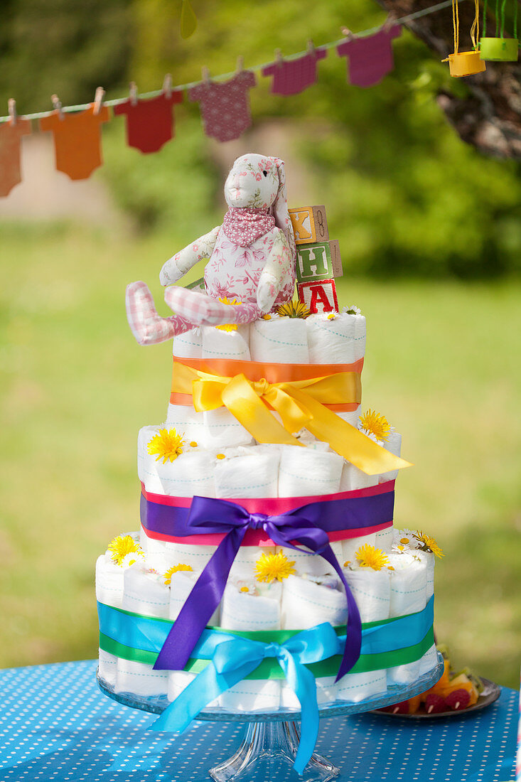 Diaper cake with ribbons in rainbow colors and onesie garland for a baby shower