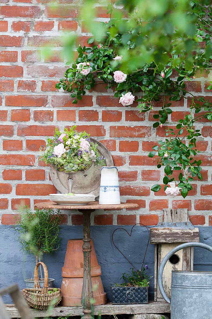 Arrangement of roses in glass goblet and climbing rose 'New dawn' on exterior house wall