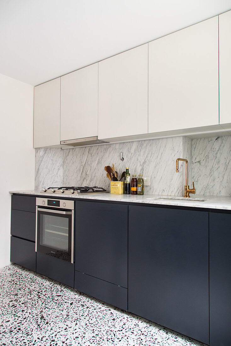 Fitted kitchen with a marble backsplash and terrazzo floor