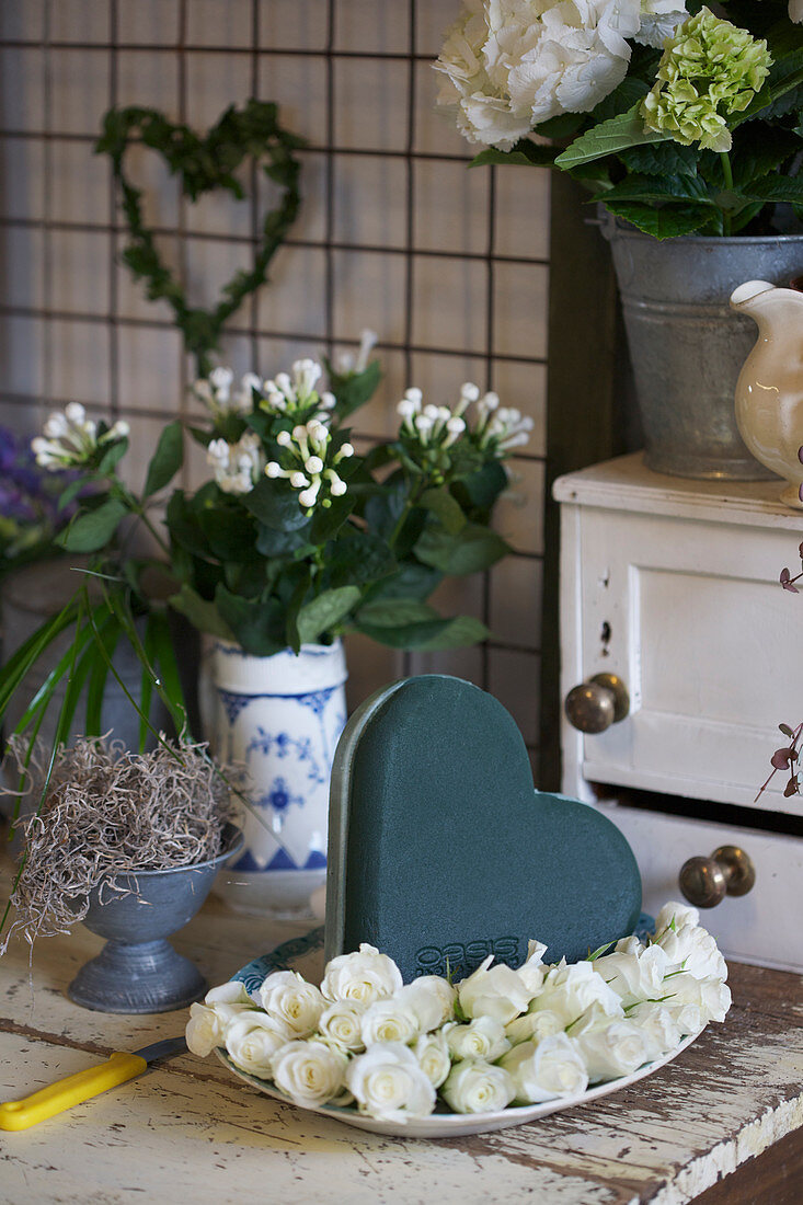 White roses, heart-shaped piece of oasis and vase of bouvardia branches