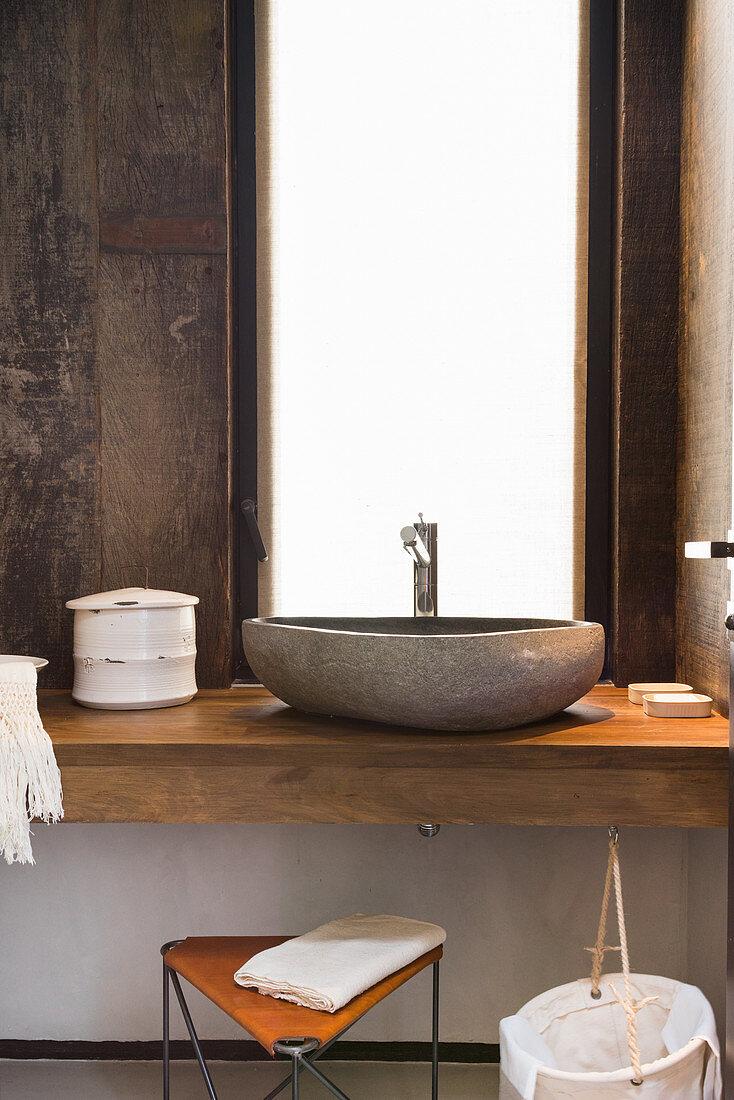 Aufsatzwaschbecken aus Stein im rustikalen Bad mit Holzverkleidung