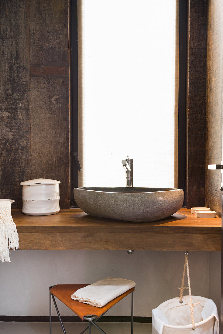 Stone, countertop sink in rustic bathroom with wood-clad walls