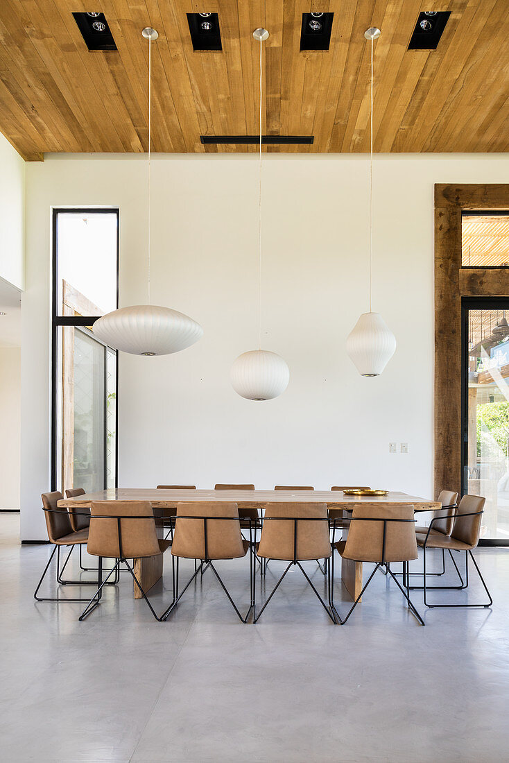 Modern upholstered chairs around large table in dining area with high ceiling
