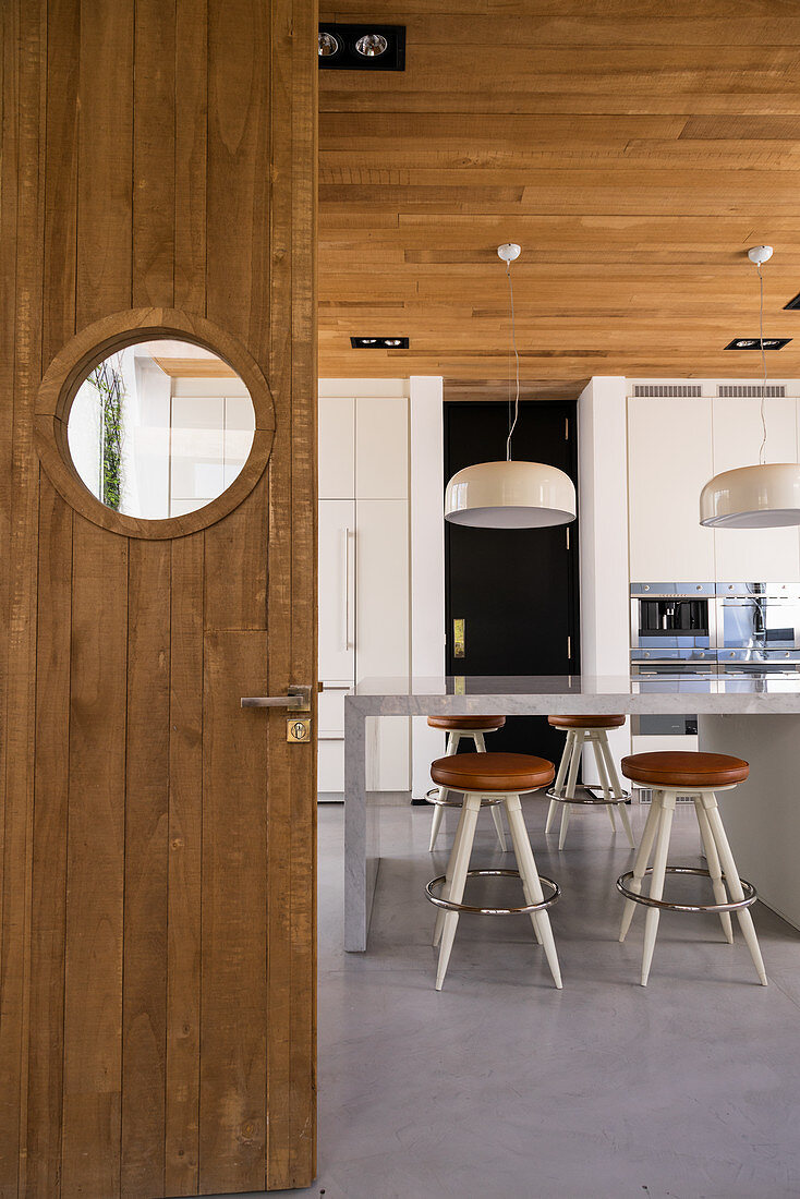 Wooden door with porthole window leading into modern kitchen with barstools at high table