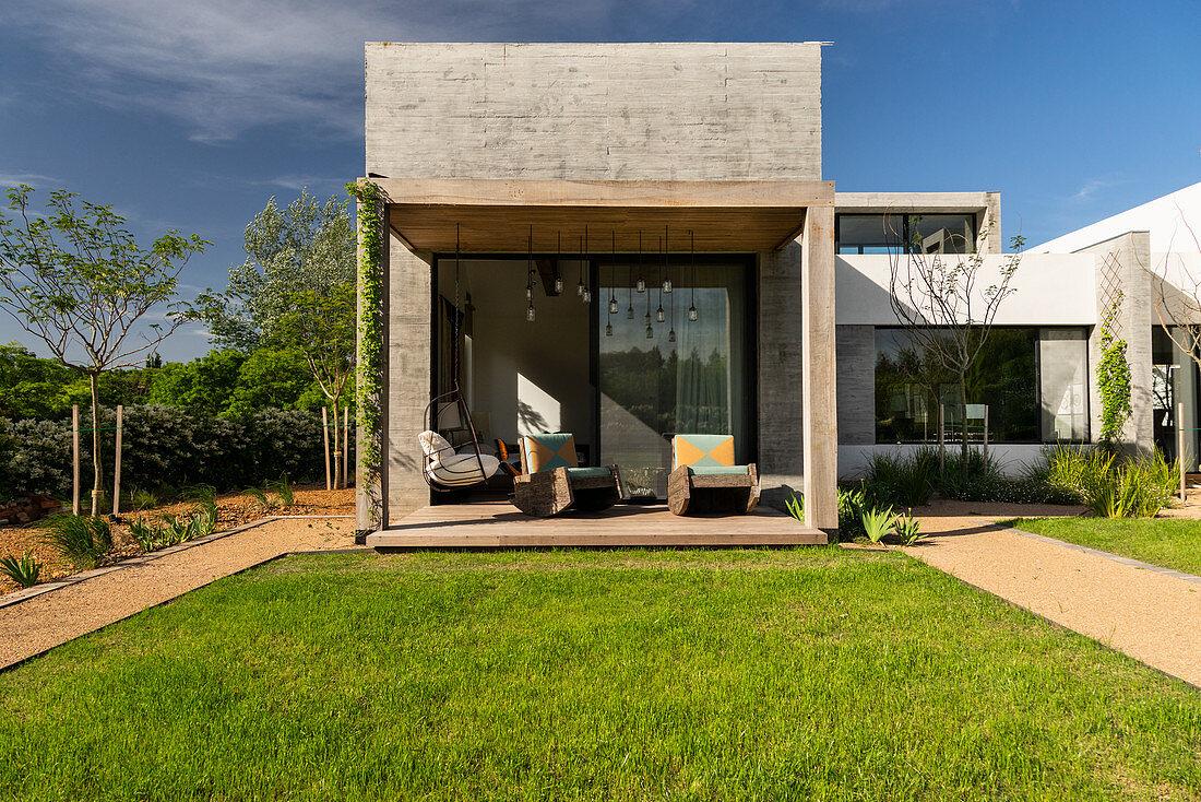 Überdachte Terrasse am modernen Architektenhaus mit Garten