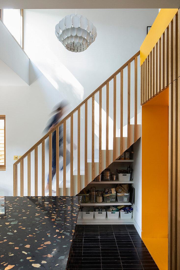 Vorratsregal unter der Treppenschräge in offener Küche