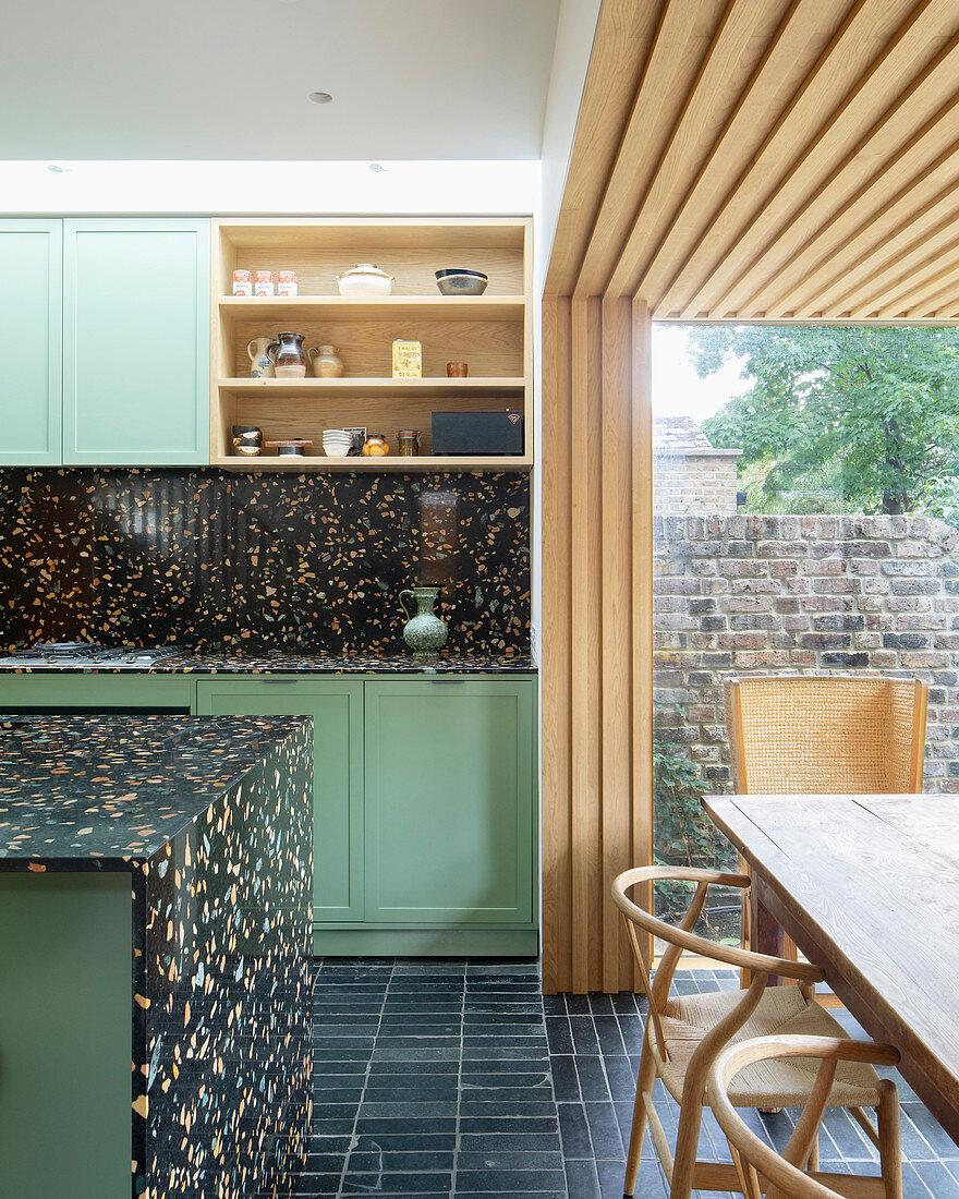 Offene Küche mit schwarzem Terrazzo und Essbereich im Anbau