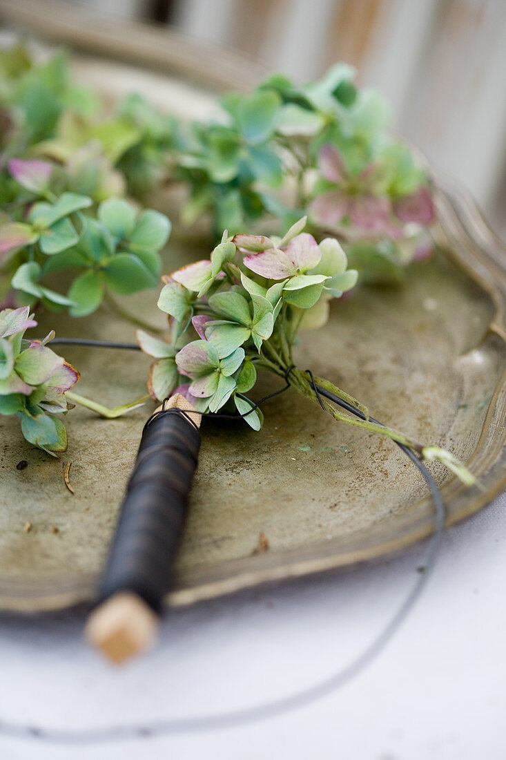 Hydrangea blossoms being tied into a wreath with wire