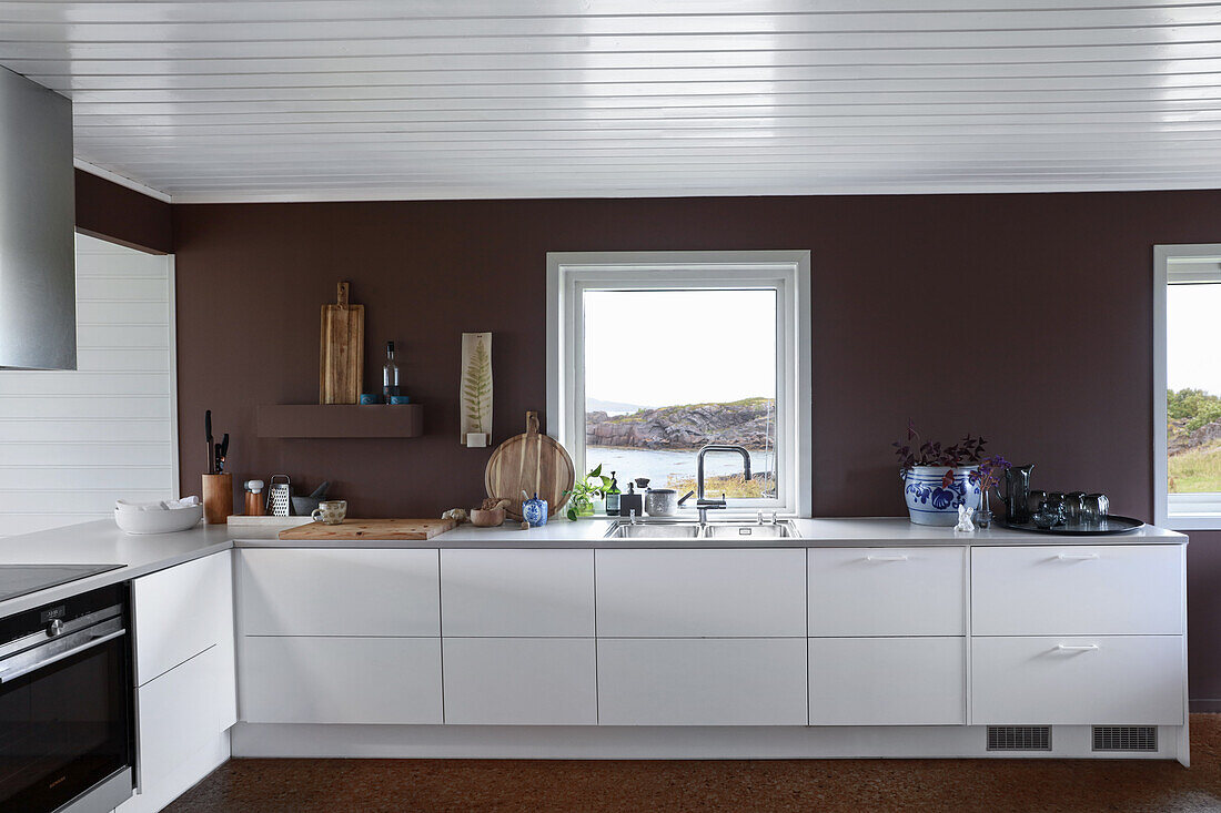 White kitchen unit in front of dark wall and window