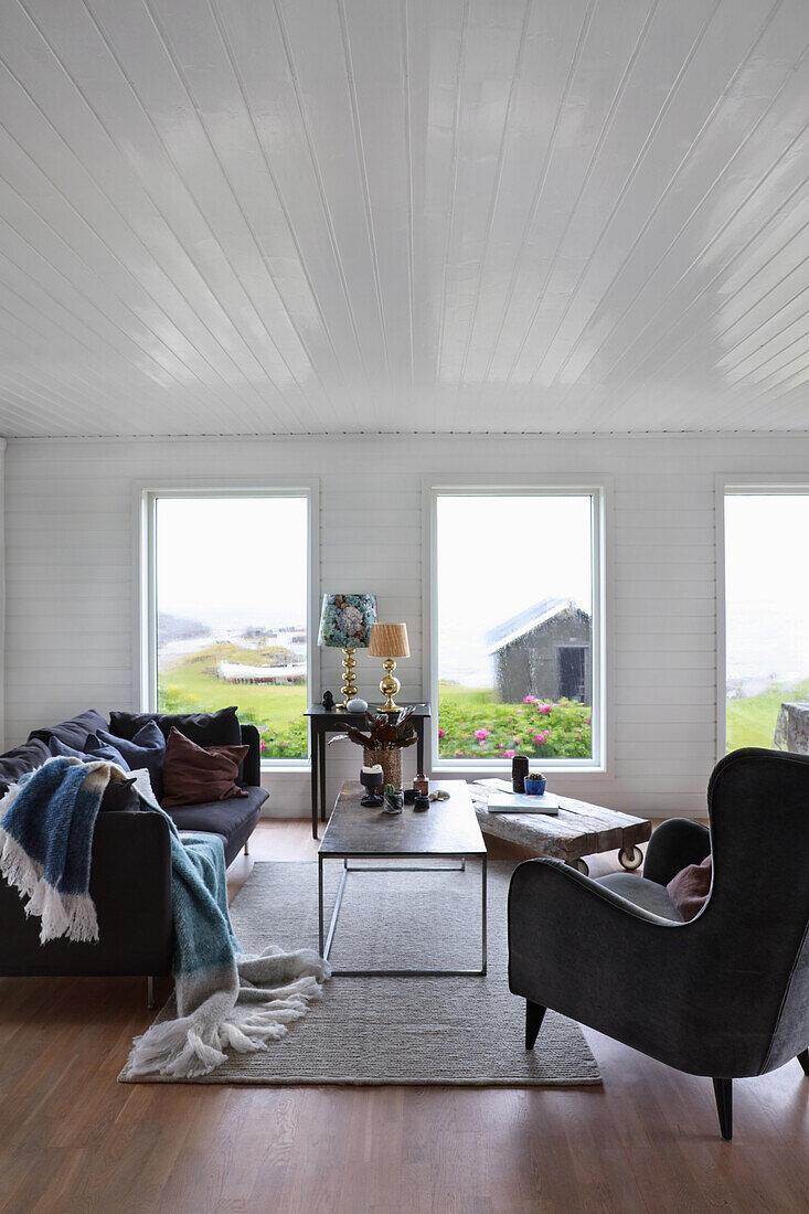 Ohrensessesl, Sofa und Couchtisch im Wohnzimmer mit weiß lackierter Holzverkleidung