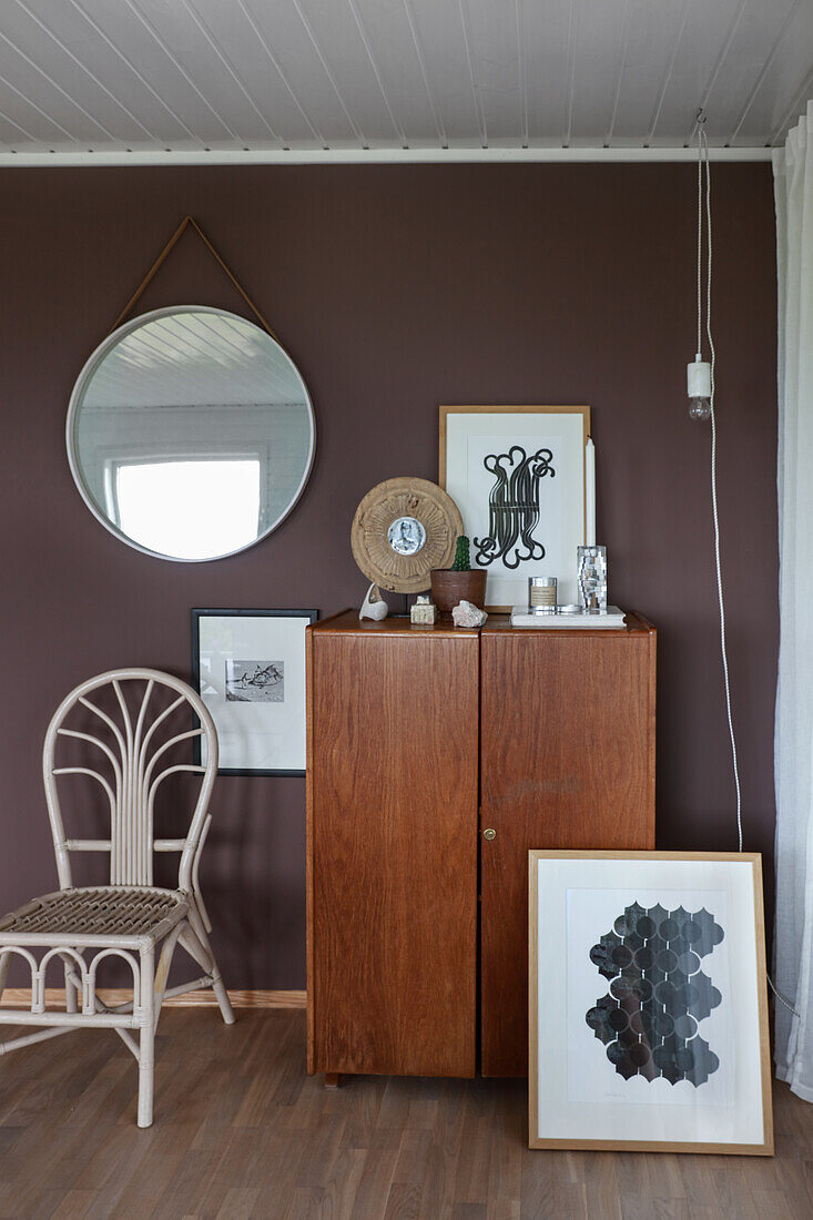 Cupboard, modern artworks, chair and mirror in corner of room with dark wall