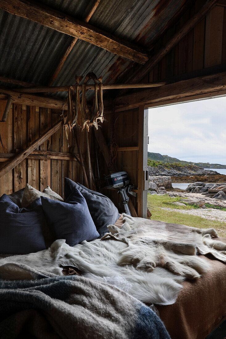 Bett mit Kissen und Tierfell in rustikaler Scheune