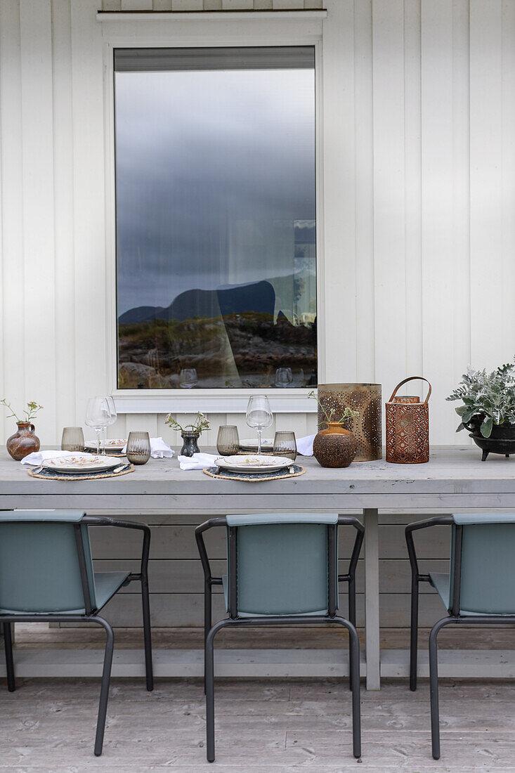 Gedeckter Holztisch mit Stühlen auf der Terrasse