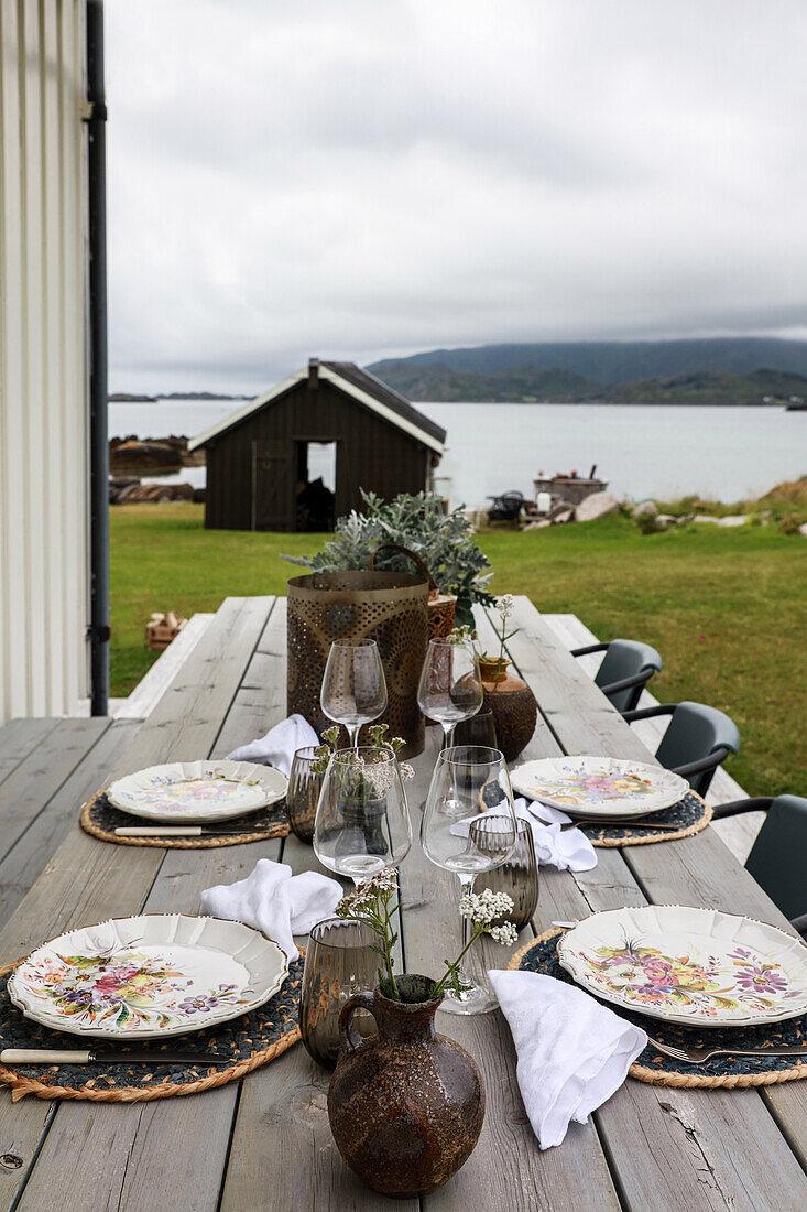 Gedeckter Holztisch mit Stühlen auf der Terrasse mit Blick auf die Lofoten
