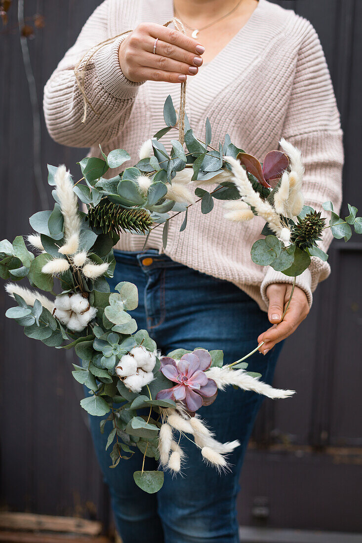 Hands holding DIY wreath made of eucalyptus twigs, pampas grass and Japanese fir