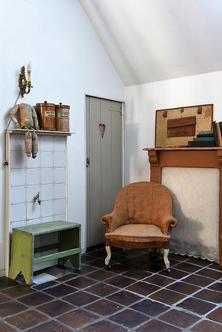 Old armchair and flea-market finds on dark terracotta tiled floor