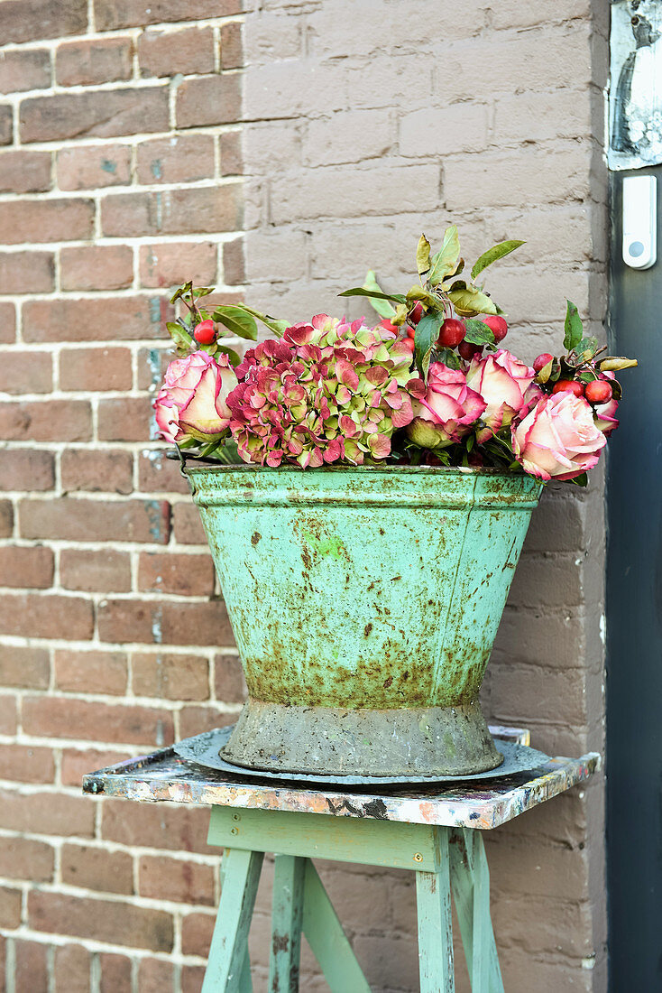 Roses, hydrangea and crababble branches in old metal bucket