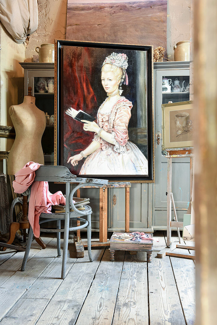 Painted portrait of woman and vintage accessories in artist's studio