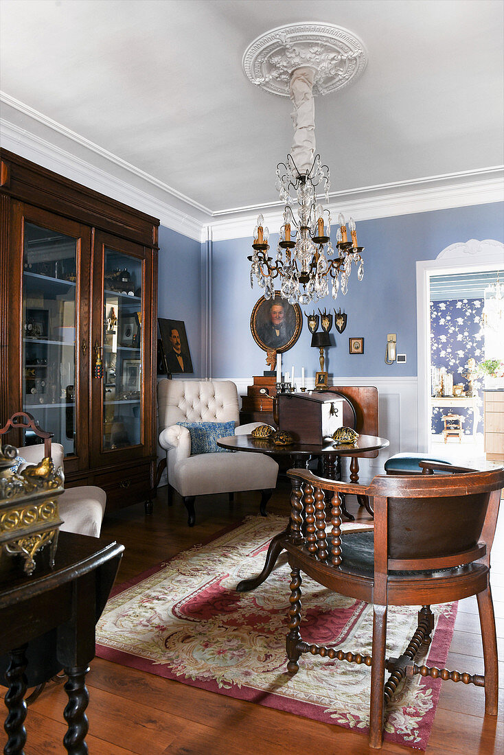 Antiques in classic living room with blue walls