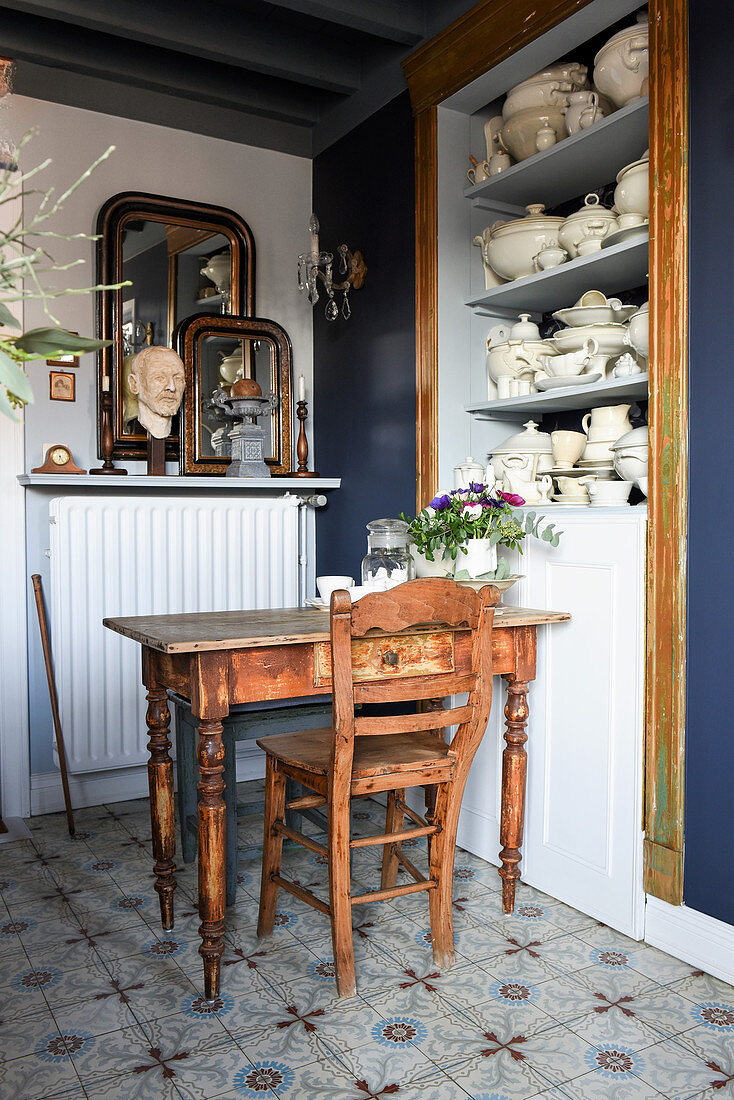 Wooden table and chair next to shelves holding old white crockery