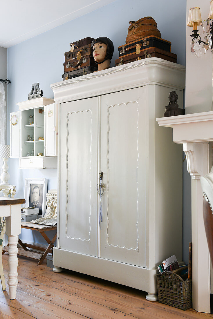 Old suitcases and bust on top of white wardrobe against pale blue wall