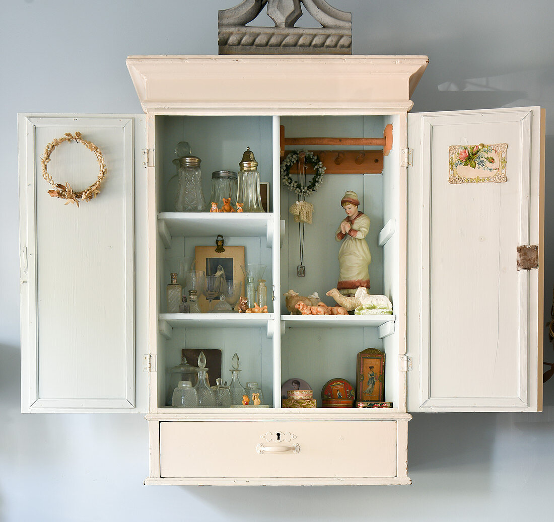 Collection of little, old bottles and vintage-style ornaments in wall-mounted cabinet