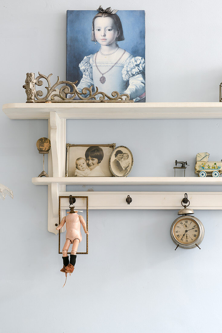 Portrait of girl and vintage ornaments on wall-mounted shelves