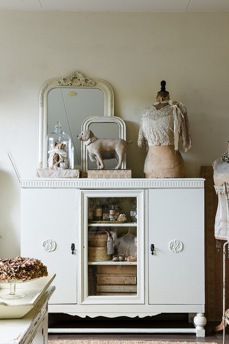 Mirror and tailor's dummy on top of dresser with vintage-style accessories