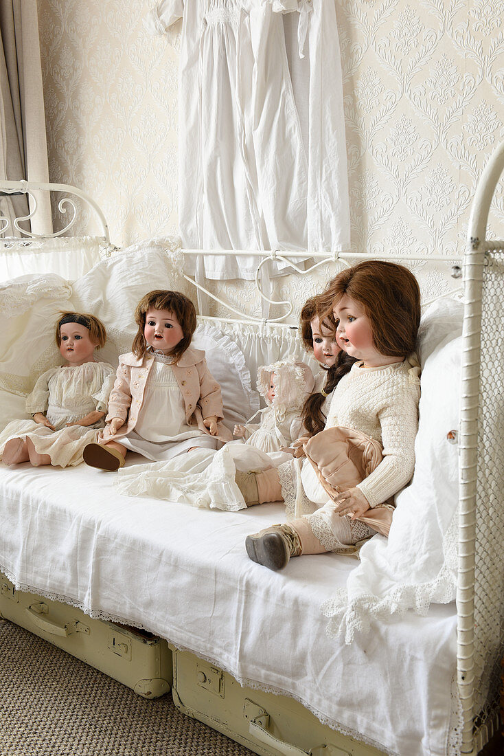 Dolls on old metal bed, suitcases and vintage-style accessories