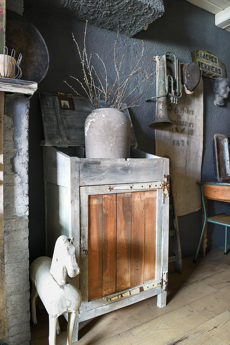 Vase of twigs in open-topped cabinet and vintage accessories against grey wall