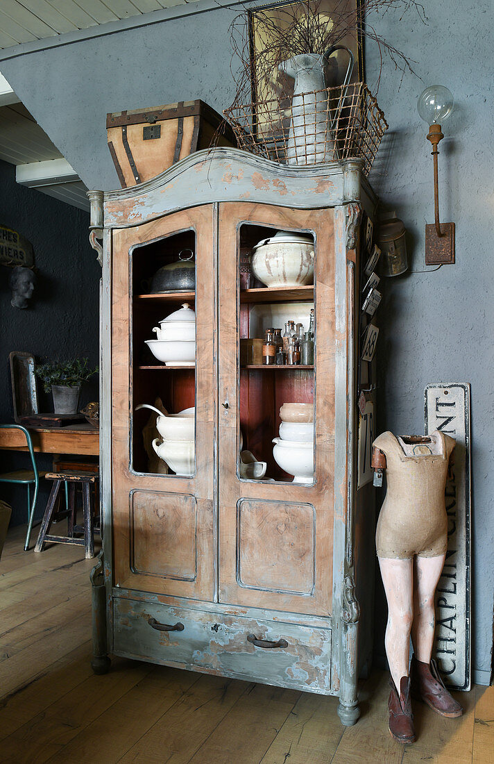 Mannequin next to old glass-fronted cabinet containing soup tureens