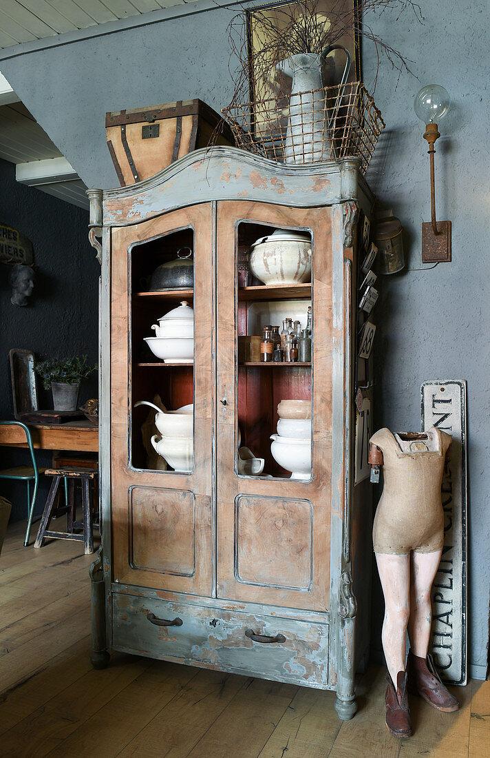 Modepuppe neben einem alten Vitrinenschrank mit Suppenterrinen